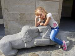 Stock Photo of Little girl sitting on the lions sculpture