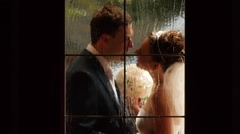 Newlyweds are kissing near a window. Enamored look the bride and groom. - stock footage