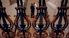 Bride and groom are kissing on the stairs in the palace. - stock footage