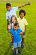 Four children are playing on the glade. - stock photo