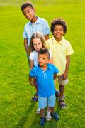Four children on the glade. - stock photo