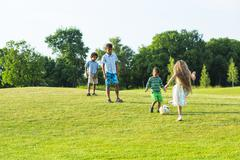 Four kids are playing on evening glade. - stock photo