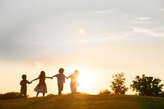 Four kids are playing on sunset. - stock photo