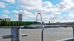 View to London eye and one of river Thames bridges from a moving boat Stock Footage