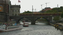 Yellow and red train passing on the railway bridge over Spree river, Berlin Stock Footage