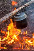 Water heating in camping kettle on fire - stock photo