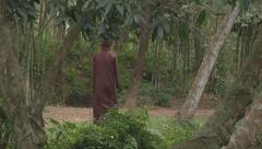 Buddhist boy going through the park in Ho Chi Minh City, North Vietnam Stock Footage