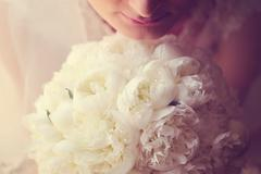 Hands of a bride holding white peonies bouquet - stock photo