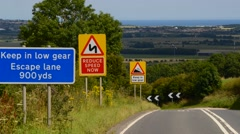 time lapse traffic passing escape lane sign on steep hill uk - stock footage