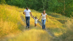 The family (father, mother and daughter) run on the way by forest background Stock Footage
