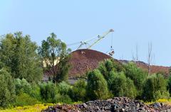 The excavator on formation of quartzite dump - stock photo