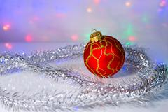 Red Christmas-tree ball and tinsel - stock photo