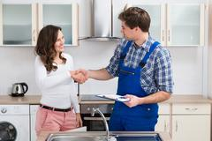 Young Woman Shaking Hands To Male Plumber With Clipboard In Kitchen Room Stock Photos