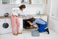Woman Looking At Male Worker Repairing Oven Appliance In Kitchen Room Stock Photos