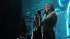 The girl Beck vocalist sings on stage into a microphone. Show business, singer Stock Footage
