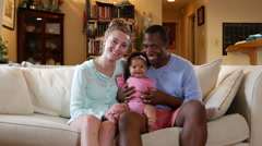 Young happy family on the couch, smile at camera Stock Footage