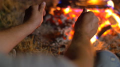 4 in 1 video!  Man sit near bonfire and heat hands. Close up view Stock Footage