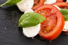 Caprese salad with mozzarella, tomato, basil and balsamic vinegar arranged on bl - stock photo