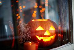 Jack-o-lantern in window - stock photo