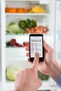 Close-up Of Person Hands Making Shopping List On Mobile Phone Display Connect - stock photo