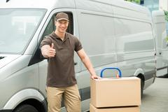 Young Delivery Man In Front Van With Cardboard Boxes Showing Thumbs Up Sign Stock Photos