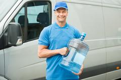 Stock Photo of Happy Delivery Man Holding Water Bottle In Front Of Truck
