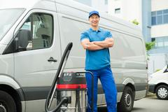 Happy Male Cleaner In Blue Uniform Standing With Vacuum Cleaner - stock photo