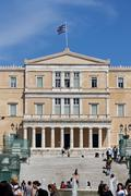 Greek Parliament building overlooking Syntagma square in Athens with people - stock photo