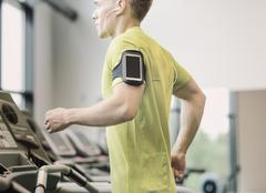 Man with smartphone exercising on treadmill in gym Stock Photos