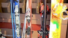 Snowboards and skis standing on a wooden rack in a sunny winter day at resort Stock Footage
