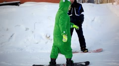 Snowboarder dressed kigurumi on piste in high mountains Stock Footage