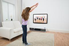 Girl Looking At Television While Doing Exercise At Home Kuvituskuvat