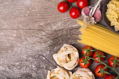 Fresh ingredients for cooking : pasta and tomato  over wooden table background - stock photo