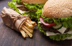 Homemade cheeseburger with tomato , cucumber and lettuce - stock photo