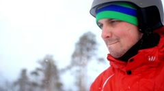Smiles snowboarder wearing a helmet and mittens on the mountain background Stock Footage