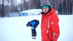 Smiles snowboarder in helmet slides down the mountain to ski lift blurred - stock footage