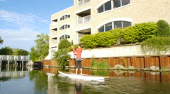 Woman rides a Stand Up Paddleboard through Traverse City, Michigan Stock Footage