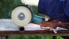 Worker in gloves cutting a metal pipe with angle grinder Stock Footage