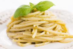 Italian pasta spaghetti with pesto sauce and basil leaf Stock Photos