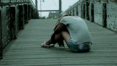 Sad desperate woman sitting on bridge after violence wide shot - stock footage