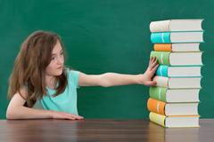 Portrait Of Girl Touching Multi-colored Stack Of Books At The Table Stock Photos