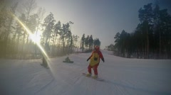 Snowboarder dressed kigurumi tiger suit with camera on piste in mountains at Stock Footage