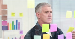 Creative businessman looking at post-it Stock Footage