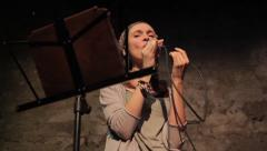 She sings the song while holding a microphone in his hand. Music,art, show, jazz Stock Footage