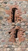 Stone wall of an old castle with loopholes Stock Photos