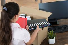 Young Businesswoman Packing Belongings In Cardboard Box At Desk - stock photo