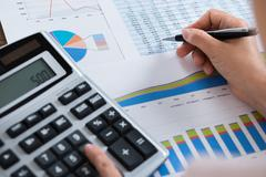 Close-up Of Businesswoman Analyzing Financial Report With Calculator At Woode Stock Photos