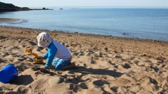 A little boy plays with toys in sand on ocean beach Stock Footage
