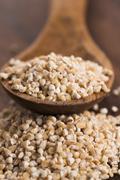 Barley groats on wooden spoon - stock photo
