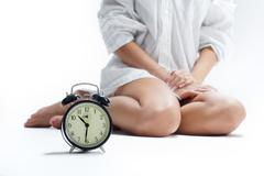 Beautiful female legs and an alarm clock Stock Photos